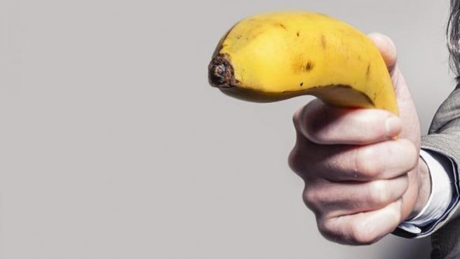 Un hombre usando un plátano como arma.