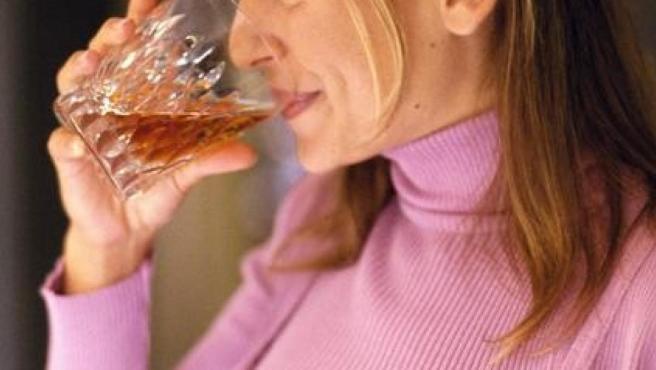 Una mujer tomando una bebida alcohólica.