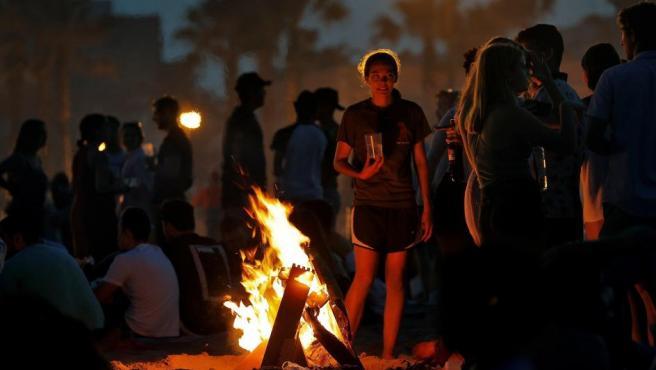 Una joven observa las llamas de la hoguera que ha encendido junto a un grupo de amigos para celebrar la Noche de San Juan, en la playa valenciana de la Malvarrosa.