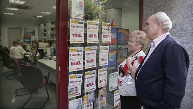 Una pareja de pensionistas miran ofertas de viajes del Imserso.