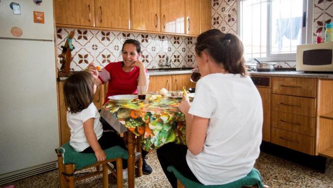 Una madre en la cocina con sus dos hijas.