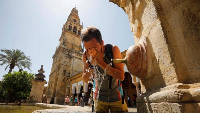 Un turista se refresca en una de las fuentes del patio de los Naranjos de la Mezquita-Catedral de Córdoba, hoy cuando las temperaturas máximas continúan en ascenso en Andalucía.