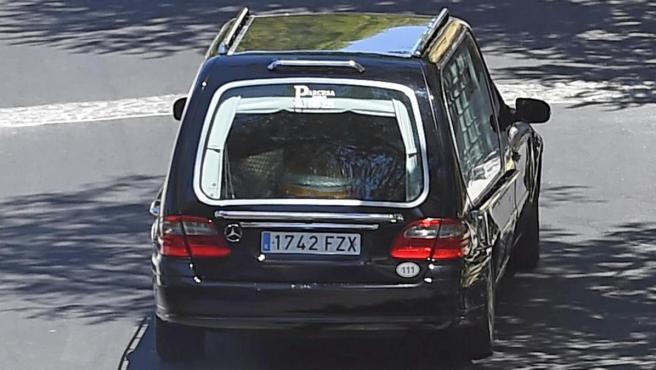 Un coche fúnebre traslada los restos mortales.