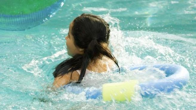 Una niña en una piscina con un flotador.