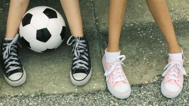 Dos niñas con un balón de fútbol.