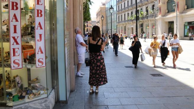 Compradores en el Portal de l'Àngel de Barcelona con un cartel de rebajas el pasado jueves.