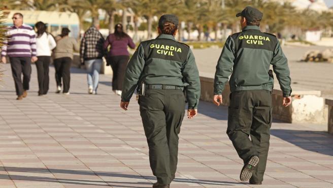 Dos agentes de la Guardia Civil en un paseo marítimo.