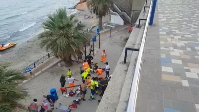 Los servicios de emergencia atienden a los dos turistas británicos que se han caído sobre una caseta de SOS, en la playa de Punta Prima, Orihuela-Costa (Alicante).