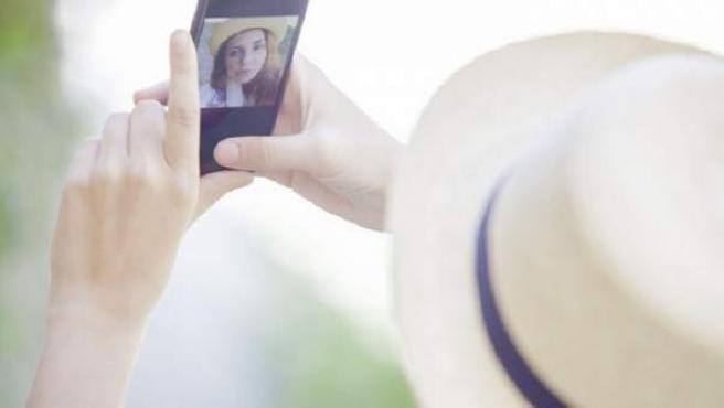 Imagen de archivo de una mujer haciéndose un selfi.