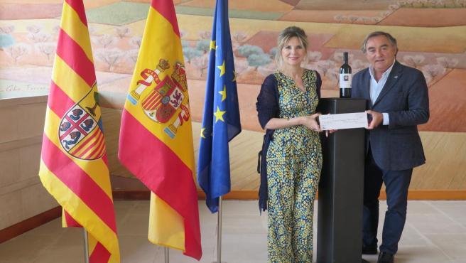 El propietario de Bodega ENATE, Luis Nozaleda, entrega el cheque solidario a la presiidenta saliente de Rotary Huesca, Eva Álvarez.