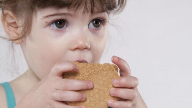 Niña comiendo una galleta.