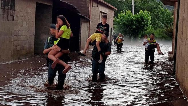 Agentes de la Guardia Civil trasladan a varios niños tras una riada en Infesta, en Monterrei (Ourense).