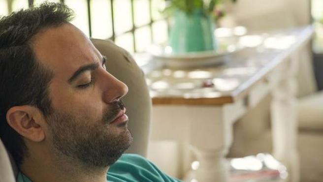 Un hombre, echando la siesta en un sofá.