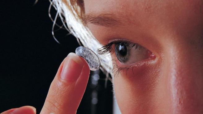 Una joven sostiene una lentilla delante de su ojo.