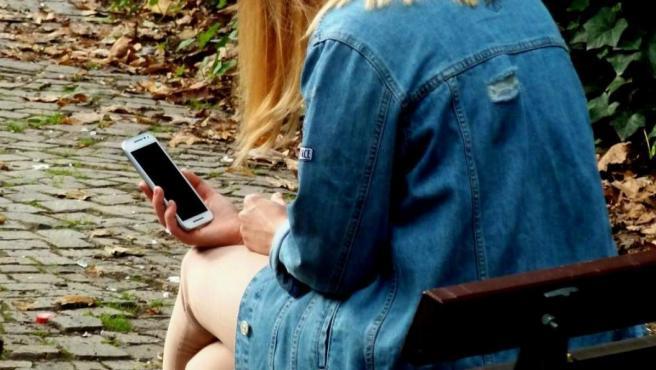 Una joven consulta su teléfono móvil, en una imagen de archivo.