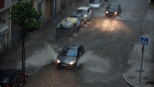 Dos vehículos circulan por una calle inundada en Ourense tras la fuerte tormenta.