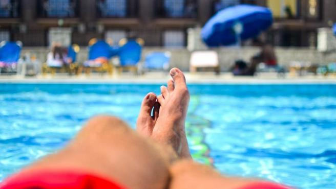 Un hombre descansa junto a la piscina.