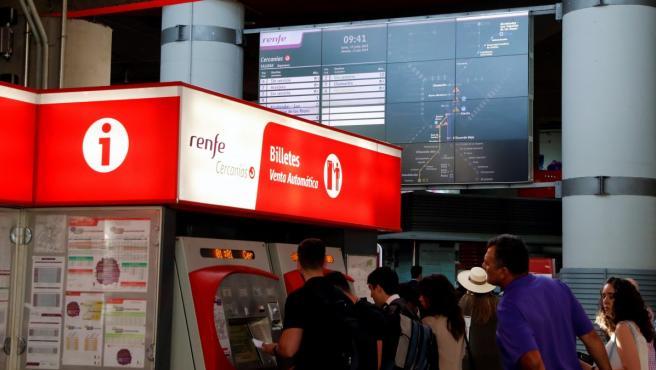 Unos viajeros sacan los billetes de tren en la estación de Atocha Cercanías.