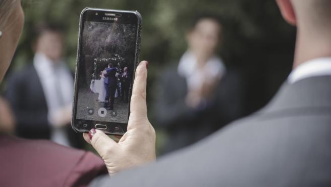 Una invitada a una boda fotografiando a los novios con su móvil.