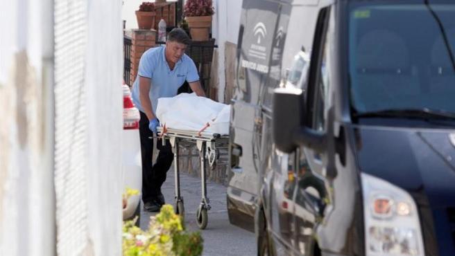 Un operario traslada uno de los cadáveres hallados en la localidad malagueña de Cortes de la Frontera, donde una mujer fue asesinada por su pareja, que se suicidó a continuación.