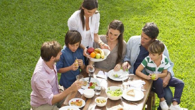 Imagen de una familia comiendo al aire libre.