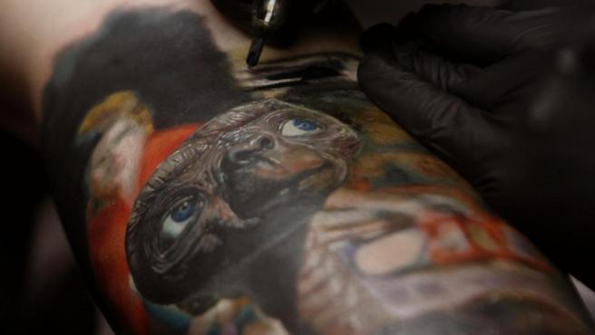 Un artista realiza un tatuaje de E.T., en el brazo de un cliente, durante la décima edición de 'Expotatuaje', en Medellín (Colombia).