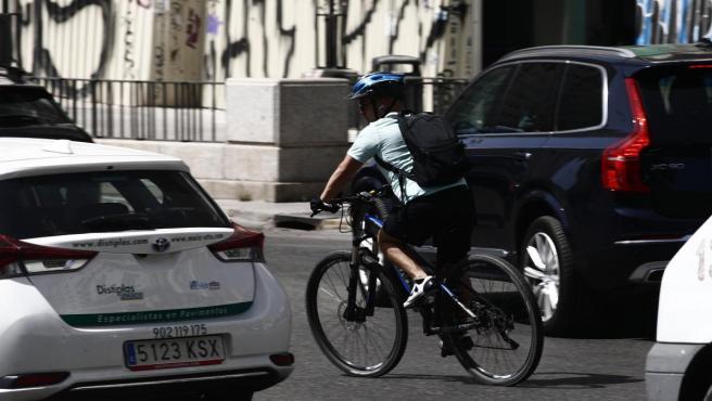 Un ciclista monta en bicicleta entre coches en la Plaza de España en Madrid.
