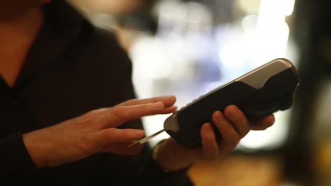 Una trabajadora realiza un cobro con datáfono.