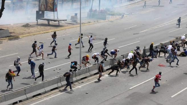 Opositores se enfrentan con la policía en una manifestación en las calles de Caracas (Venezuela).