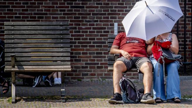 Una pareja se resguarda de los rayos de sol bajo un paraguas, este jueves en Ámsterdam (Holanda). La temperatura alcanzó los 40,4 grados en Holanda, batiendo récords históricos.
