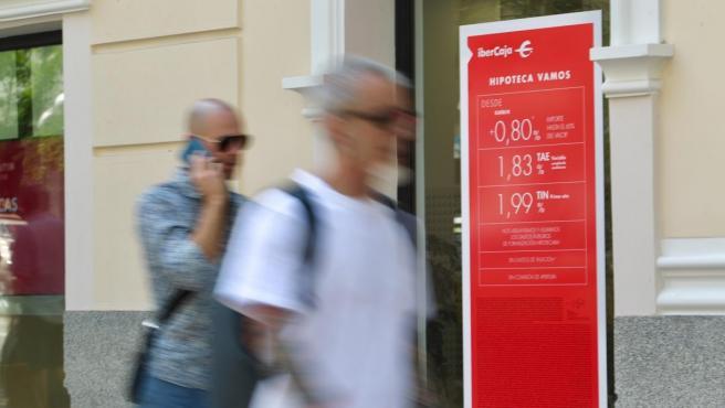 Dos personas pasan por delante de una oficina de Ibercaja con propaganda de ofertas hipotecarias.