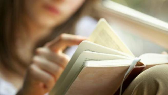 Una mujer leyendo un libro.