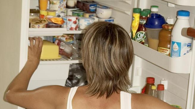 Una mujer busca alimentos en su nevera.