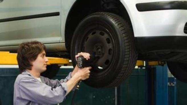 Un trabajador cambiando las ruedas a un coche en un taller mecánico.