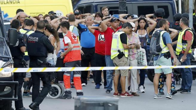 Un grupo de gente con los brazos en alto ante el despliegue policial en el lugar del atentado ocurrido en las Ramblas de Barcelona.