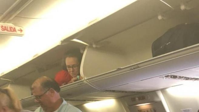 Una azafata de Southwest Airlines se mete en el compartimento de maletas de un avión.