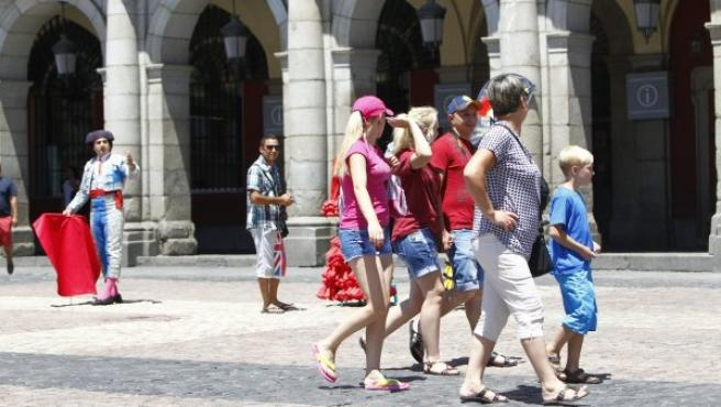 Un figurante invita a los turistas que pasean por la Plaza Mayor de Madrid a fotografiarse con él.
