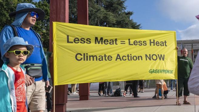Activistas de Greenpeace sujetan un cartel que condena el consumo de carne.