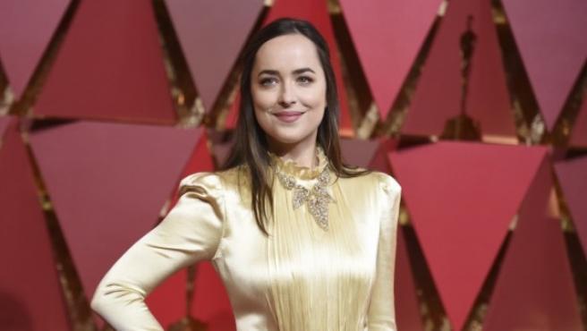 Dakota Johnson, la actriz de 50 sombras de Grey, posa elegantísima en la alfombra roja de los Premios Oscar. El dorado, una vez más, entre los colores más elegidos por las asistentes.