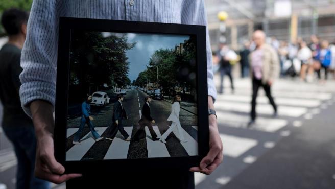 Un fan de los Beatles sostiene la foto de la famosa portada de Abbey Road junto a los estudios del mismo nombre, en Londres.