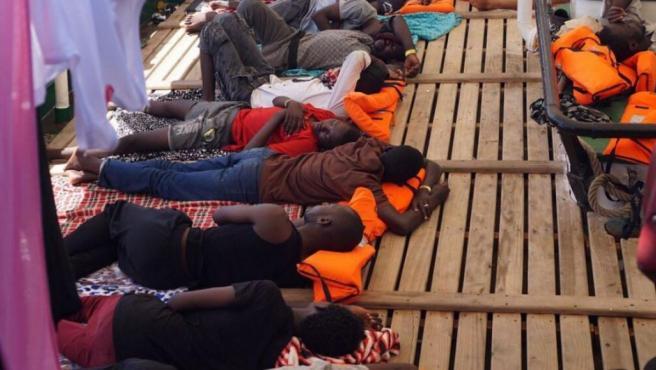 Inmigrantes tumbados en la cubierta del barco Open Arms.