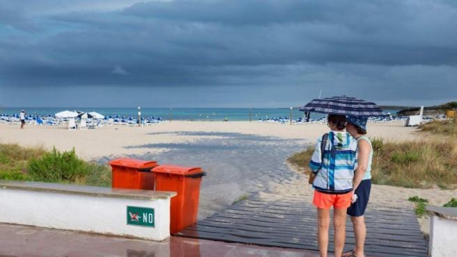 Dos mujeres se resguardan en un paraguas en la playa durante un día de lluvia.