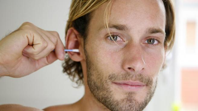 <p>Un hombre se limpia el oído con un bastoncillo de algodón.</p>