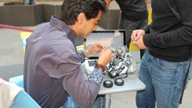 Un ingeniero preparando su robot de pelea.