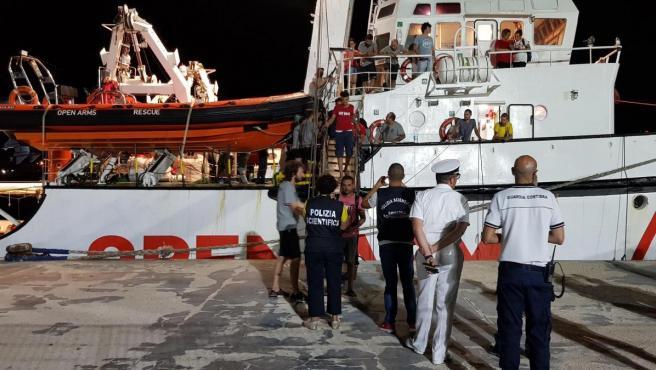 Los inmigrantes del barco Open Arms desembarcan en el puerto de Lampedusa (Italia).