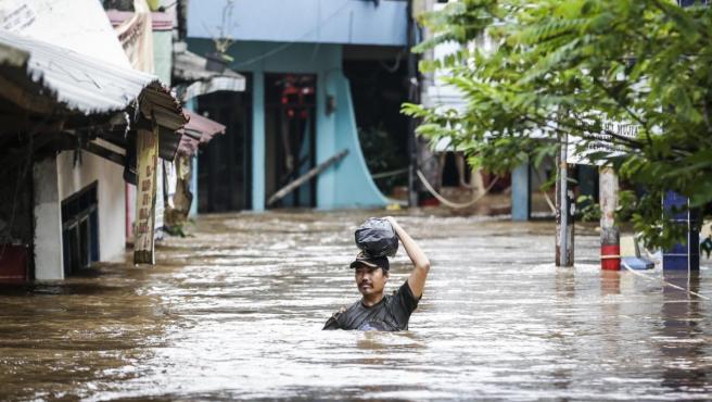 Un hombre camina con el agua prácticamente al cuello por una calle inundada en un barrio de Yakarta (Indonesia).