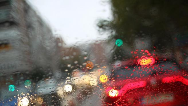Una calle con retenciones por la lluvia, vista desde el interior de un coche con los cristales empapados.