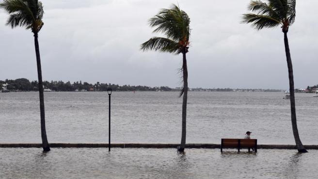 Un hombre observa desde una banco, en un paseo inundado, la subida del nivel del mar antes de la llegada del huracán Dorian, en Palm Beach, Florida (EE UU).