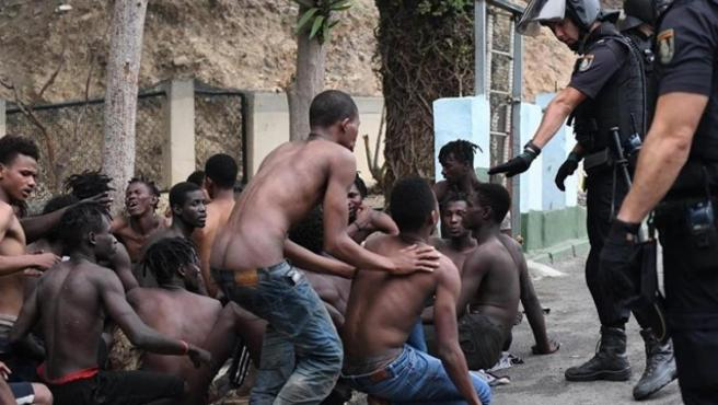 Inmigrantes y efectivos policiales tras el salto masivo a la valla de Ceuta el 30 de agosto.