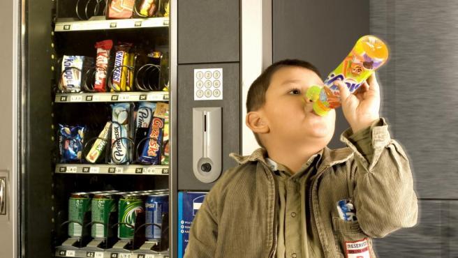 Un niño bebe un refresco junto a una máquina con bebidas y bollería industrial.